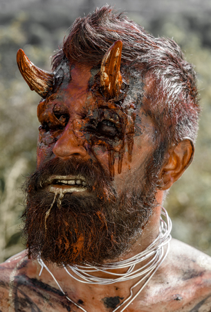 Halloween dragon creature on natural environment. Demon man with beard. Satan with red blood and wounds on face skin. Devil head with bloody horns. Temptation, hell, evil, horror, darkness concept.