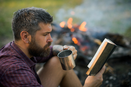 Camping, hiking, lifestyle. Hipster hiker with book and mug at bonfire on nature. Sustainable education, environment concept. Man traveler read and drink at campfire flame. Summer vacation, activity.