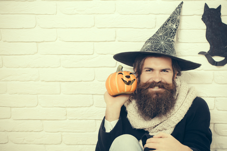 Halloween man in witch hat happy smiling on brick wall. Hipster with pumpkin and black cat symbol. Bad luck concept. Evil spell and magic. Autumn holidays celebration, copy space