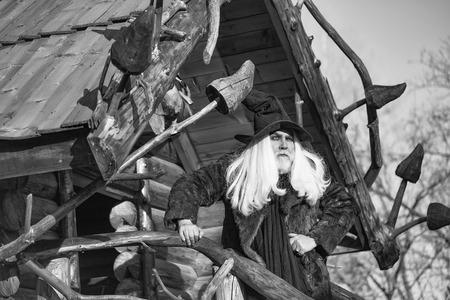 古いドルイド男は長い黒のハロウィーン帽子スタンド ログ家背景に晴れた日に屋外で髪と髭を銀します。 写真素材