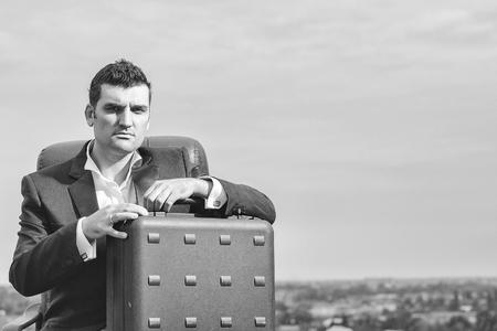 黒のフォーマルなジャケットと革オフィスの腕椅子曇り空の背景コピー スペースに屋外に簡単なケースと白いシャツで深刻な顔でハンサムな男性ビ