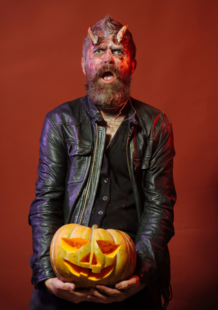 Halloween man demon hold pumpkin on brown background. Devil with bloody horns on head. Satan with beard, wounds, red blood on face. Autumn holidays concept. Jack o lantern. Stock Photo