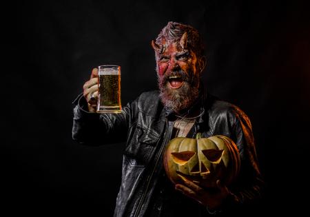 Halloween slechte gewoonten en verslavingsconcept. Duivel glimlach met glazen mok. Man met satan hoorns houden pompoen. Feestviering en feest. Hipster demon drinkt bier op zwarte achtergrond. Stockfoto