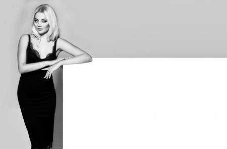pretty girl or cute woman with long platinum blonde hair and fashionable makeup on face in sexy glamour black dress on white and grey background, copy space Banco de Imagens