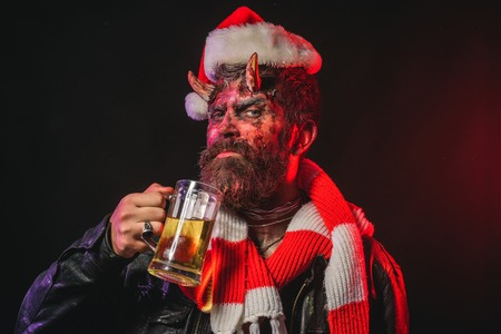 Halloween christmas holiday, party celebration. Hipster with satan horns hold glass mug. Devil in santa hat and scarf. Man demon drink beer on black background. Bad habits and addiction concept.