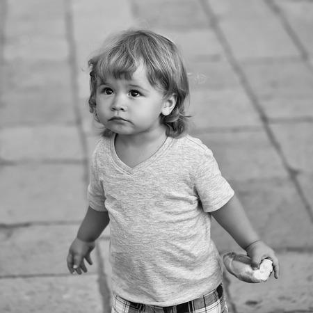 Fotoportret van schattige blonde blonde, hazelogige jong geitje, klein, klein kind, babyjongen, vervelend, vest, vasthouden, broodje, in, hand, kijken naar boven, op, flag-stone, bestrating, op, vage, grijze achtergrond, vierkant, beeld