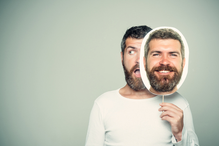 Barber fashion and beauty. Man with long beard and mustache. Hipster with happy and surprised face hold portrait nameplate. Feeling and emotions. Guy or bearded man on grey background., copy space