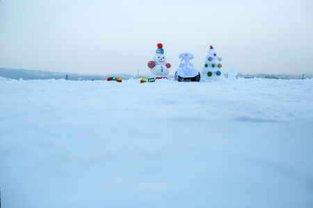 Winter holidays celebration concept. Festive surprise and presents. Tricycle and toy car on snowy background. Snowman and snow xmas tree on blue sky. Christmas and new year, copy space