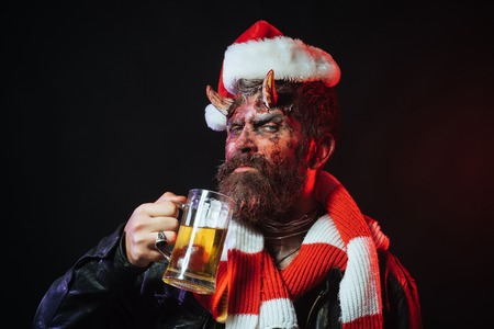 Halloween christmas man demon drink beer on black background. Bad habits and addiction concept. Devil in santa hat and scarf. Holiday celebration and party. Hipster with satan horns hold glass mug.