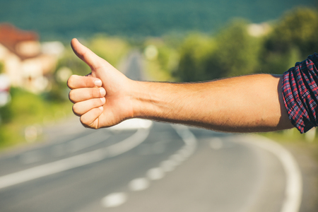 Travel, trip, vacation, wanderlust. Hitchhiker sign on road. Thumbs up male hand gesture outdoors. Hitchhiking, hitching, thumbing, auto stop concept. Imagens - 88757571