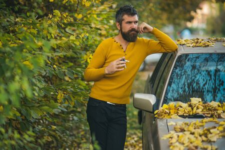 travelling and fall holiday. Man with beard at car. man in autumn forest. Autumn guy outdoor. adventure and wanderlust.