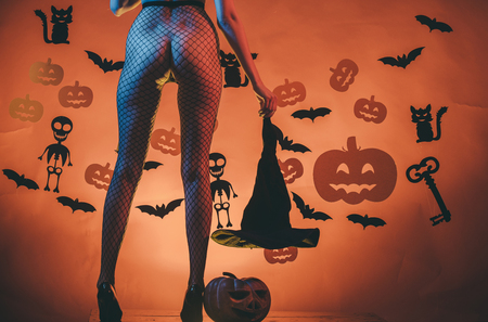 Halloween Holiday. Halloween sexy female legs in fishnet tights and shoes. Legs of girl on skeleton and bat background. party and celebration. buttocks of woman at pumpkin hold witch hat. Stockfoto
