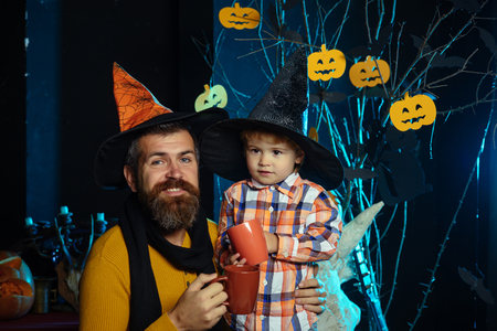 Halloween Boy kid with happy face and bearded man at pumpkin. Father and small son drink from tea or milk cup. Halloween Holiday and celebration. party and celebration. man and child in witch hat.