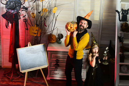 Girl and bearded man with smiling faces near blackboard in carnival room. Wizard and little witch show silence sign holding pumpkin and candlestick. Dad and kid with Halloween decor. Halloween concept