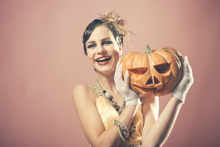 Halloween, Beauty and vintage fashion. Girl in yellow dress with pumpkin. halloween holiday and party celebration. Pin up pretty fashion model on pink background. happy Woman with retro hair, makeup.