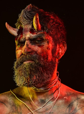 Halloween man demon on black background. Holiday celebration, cosplay. Devil with bloody horns on head. Hell, death, evil, horror concept. Satan with beard, red blood, wounds on face. Stock Photo
