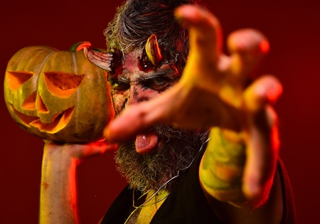 Halloween trick or treat. Satan with bloody horns, beard, blood, wounds. Darkness and light concept. Demon stretch zombie hand with jack o lantern. Man devil hold pumpkin on red background.