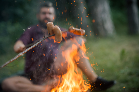 Picnic, barbecue, cooking food concept. Sausages roasted on bonfire flame with blurred man hipster on natural background. Summer camping, hiking, vacation.
