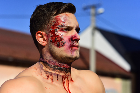 Halloween Party and bloody horror. Holiday and celebration. Dead demon with spooky makeup. man with zombie face. Halloween guy with blood and wounds