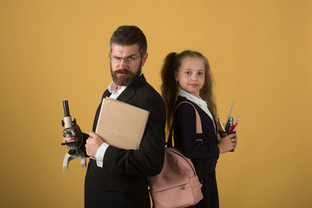 Kid and dad hold microscope, book and stationery. Home schooling and back to school concept. Girl with bag and bearded man. Father and schoolgirl with serious and smiling faces on orange background