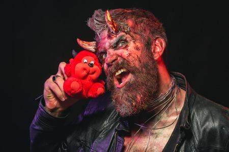 黒の背景に赤い悪魔のおもちゃでハロウィン男轟音。マスコット、贈り物、プレゼントサタンホーンとヒップスターは、血まみれの傷は柔らかいモ 写真素材