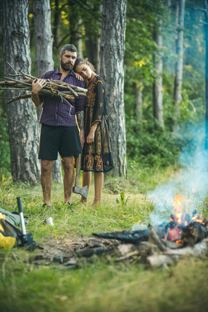 Woman hug man lumberjack with axe and bunch of firewood. Couple in love make bonfire in forest. Camping, hiking, lifestyle. Summer vacation concept.