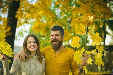 Autumn happy couple of girl and man outdoor. Nature season and fall holiday. Love relationship and romance. Couple in love in autumn park. Man and woman at yellow tree leaves. Stock Photo