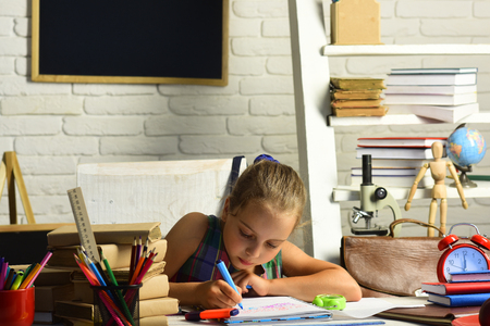 Girl with serious face does homework. Pupil with books and school supplies. Childhood and back to school concept. Kid with colorful stationery on white wall background.