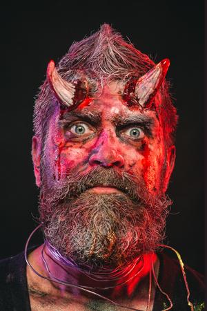 Halloween-satan met baard, rood bloed, wonden op het gezicht. Hell, death, evil, horror concept. Feestviering, cosplay. Demon met bloedige hoorns op het hoofd. Mensenduivel op zwarte achtergrond.