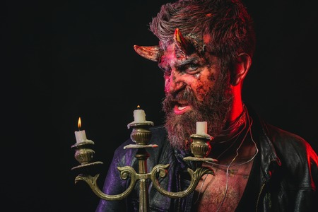 Halloween flesh, soul, darkness, light concept. Man demon hold candlestick on black background. Satan with beard, red blood, wounds on face. Devil with bloody horns on head. Holiday, party celebration