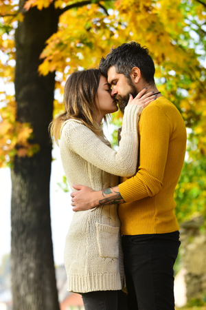 Man and woman at yellow tree leaves. Autumn happy couple of girl and man outdoor. Love relationship and romance. Nature season and fall holiday. Couple in love in autumn park.