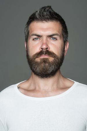 Feeling and emotions. Guy or bearded man on grey background. Man with long beard and mustache. Barber fashion and beauty. Hipster with serious face.