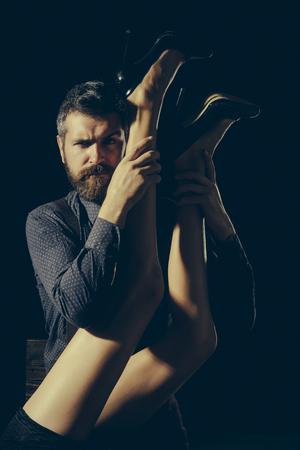 Mens in overhemd op zwarte achtergrond wordt geïsoleerd die. Benen van vrouw in schoenen bij de mens met baard. Romantiek en verliefd. Liefde en relaties, domineren. Jongen aan tafel met vrouwelijke benen.