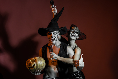 Halloween Holiday and celebration. Halloween couple with makeup on brown background. woman and man has happy face in witch hat. Couple in love with pumpkin and wine glass. Zombie party and horror.