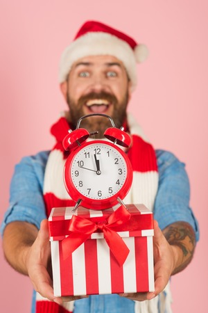 boxing day: Christmas present box and alarm clock in blurred man hands. Boxing day concept. Hipster in santa hat, scarf smile on pink background. New year, xmas holidays celebration. Time to celebrate.