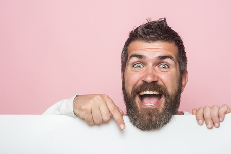 man with long beard on happy face with paper on pink background, presenting product