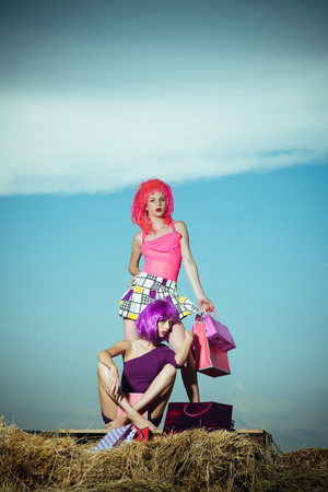 women in colorful wig hair with shopping bag or present pack on hay in summer or spring holiday on sunny blue sky