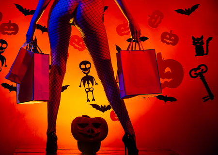 Halloween buttocks of woman at pumpkin hold shopping bag. Halloween Holiday celebration. Legs of girl on skeleton and bat background. shopping and party package. sexy legs in fishnet tights and shoes. Banco de Imagens