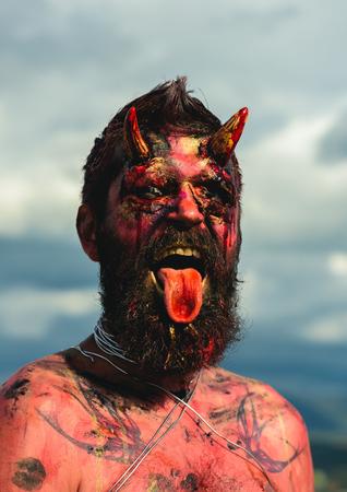 Halloween-duivelskop met bloedige hoorns. Demon man met baard toont tong. Satan met rood bloed en wonden op het gezicht. Vampier of draak met open mond. Hell, evil, horror, darkness concept.