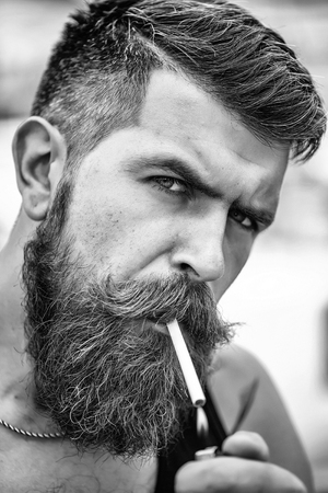Frown handsome bearded man with beard moustache and gray hair stylish hipster male smoking cigarette outdoor, closeup