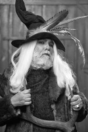 暗い背景に手に鹿の角で鳥の羽と毛皮のコートとハンターハットで長い灰色の髪のひげを持つドルイドの老人