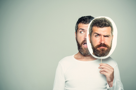 Guy or bearded man on grey background. Barber fashion and beauty. Man with long beard and mustache. Hipster with surprised and sad face hold portrait nameplate. Feeling and emotions., copy space Imagens