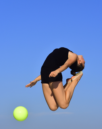 free education: Gymnastic school and energy. Woman gymnast in black sportswear with green ball. Sport and success. Flexibility in acrobatics and fitness health. Workout of girl on blue sky background. Stock Photo