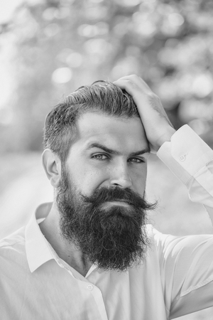 Handsome young stylish hipster man with long beard in white shirt standing outdoor on natural background sunny day outdoor