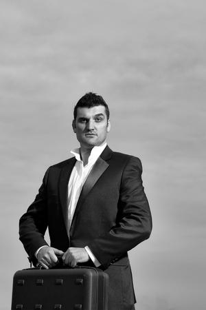 黒いフォーマルジャケットと白いシャツに驚いた顔をしたハンサムな男性ビジネスマン、曇った空の背景に革のオフィスアームチェアの屋外にブリ