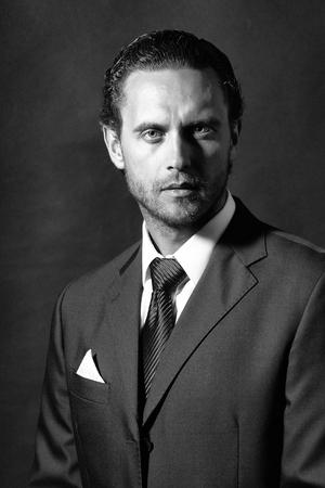 형태가없는 얼굴 및 넥타이와 흰 셔츠와 스튜디오 배경에 자켓 주머니에 손수건 검은 공식적인 양복에 헤어 스타일 잘 생긴 남자