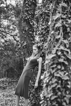 Beautiful young woman with red lips in fashion dress standing in the green vine near forest trees
