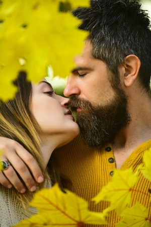 Man and woman at yellow tree leaves. Couple in love in autumn park. Autumn happy couple of girl and man outdoor. Love relationship and romance. Nature season and fall holiday. Stock Photo