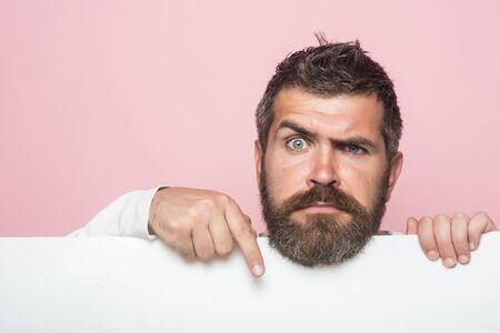 감정과 감정. 이발사 패션 및 뷰티 마케팅. 진지한 얼굴을 가진 힙 스터가 종이를 개최. 남자 또는 분홍색 배경에 수염 난 사람. 긴 수염과 콧수염을 가