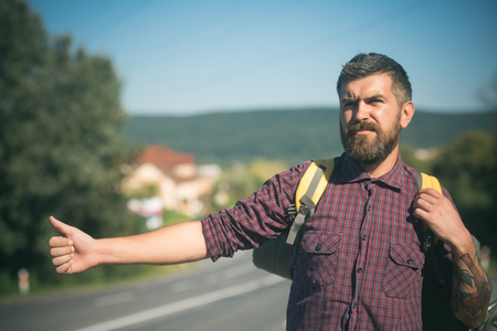 Adventure, discovery, wanderlust. Tourist traveler travel auto stop. Man with backpack hitchhiking on road. Summer vacation concept. Hipster hiker show thumbs up hand gesture on sunny day.
